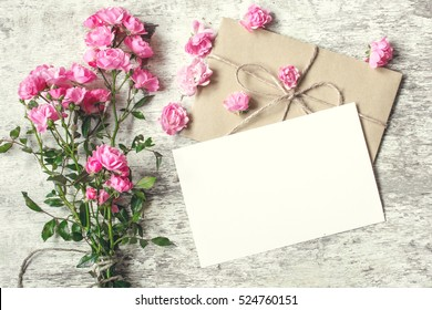 blank white greeting card with pink rose flowers bouquet and envelope with flower buds on white wooden background. vintage toning.top view. mock up