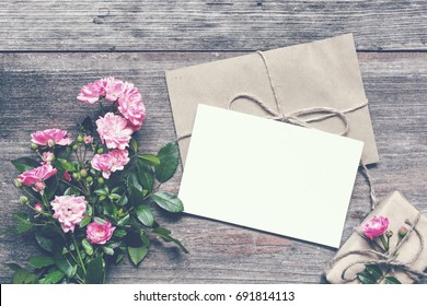 blank white greeting card with pink rose flowers bouquet and envelope with gift box on rustic wooden background. vintage toning .top view. mock up
