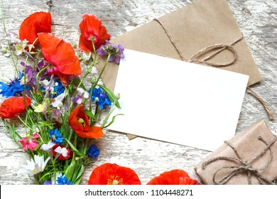 blank white greeting card with summer wildflowers bouquet and gift box over rustic wooden background. top view. mock up