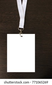 Blank White ID Card Badge with Clasp and Lanyards Isolated on Black Wooden Background. Corporate Identification Empty Credential for Event Staff, Press Concept Mock Up Design.