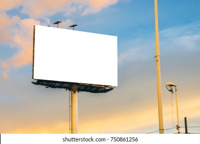 Blank white isolated billboard at the highway with a cloudy sky during the sunset in the background
