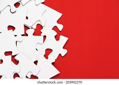 Blank white jigsaw puzzles on a bright red paper background with copy space