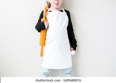Blank white kid's apron worn by female child standing holding baking props, kids' apron apparel mockup