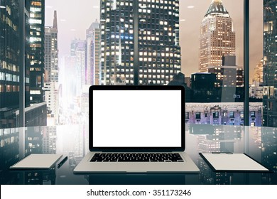 Blank white laptop screen on glassy table in modern office with night megapolis city view, mock up