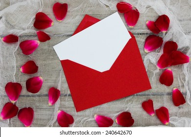 Blank white letter or note card and red envelope with red flower petals on shabby white netting and wood background; Valentines Day, Mothers Day, and love concept background with white copy space