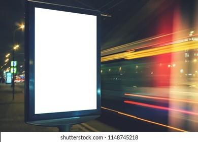 Blank white lightbox at night. Mock-up design concept. Car lights in motion blur