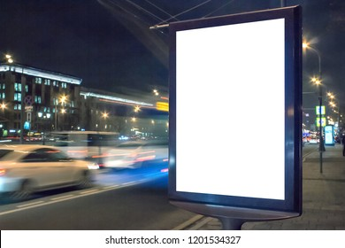 Blank white lightbox at night. Mock-up design concept. Car lights in motion blur