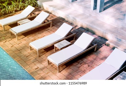 Blank white loungers mock up near swimming pool near luxury hotel. Lounge mockup for summer holidays. Sunbed for sunbathing in the inn template.