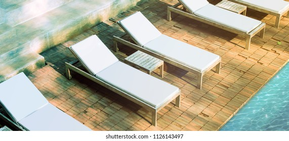 Blank white loungers mockup near swimming pool near luxury hotel. Lounge mock up for summer holidays. Sunbed for sunbathing in the inn template.