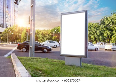 Blank white mock up of vertical light box in a bus stop in beautiful weather