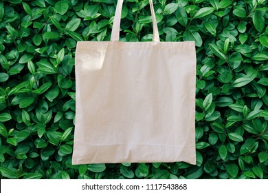 Blank White Mockup Linen Cotton Tote Bag on Green Bush Trees Foliage Background. Eco Nature Friendly Style. Environmental Conservation Recycling Concept. Template for Artwork Text. Japanese