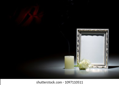 Blank white mourning frame, with smoky candle and white rose, on dark background with red decoration