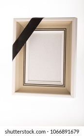 blank white mourning picture frame with black ribbon on bright background for obituary card