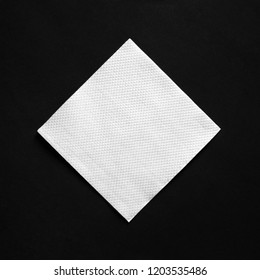 Blank white napkin on black paper background with copy space. Flat lay.