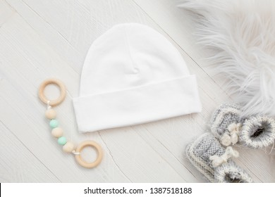 Blank white newborn baby hat with rattle and booties, baby apparel mock up