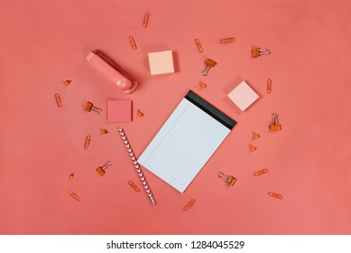 Blank white note pad paper, pencil, stapler, thumb tacks, paper clips, and adhesive paper over coral color background with free space for text. Image shot from top view.