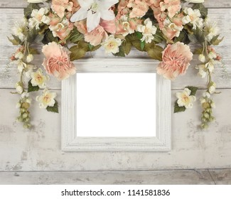 A blank white old vintage antique frame mockup with a pink pastel flower wreath on a wood textured background. Use it for a wedding or romance flat lay