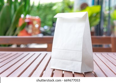 Blank white paper bag for taking away food on a wooden table