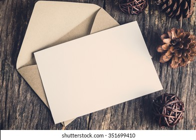 Blank white paper card with brown envelop and pine cones on old wooden table with vintage and vignette tone