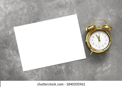 Blank white paper card mockup and gold alarm clock on gray concrete background. Template for your design. Top view, flat lay. Minimal stationery scene