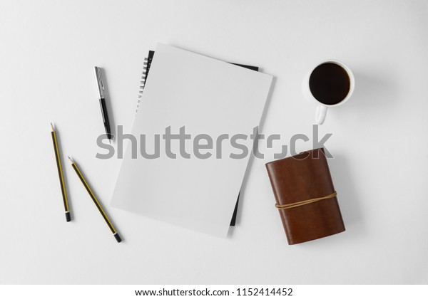 Blank white paper and coffee cup on white background.
