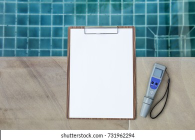 Blank white paper on wood clipboard with digital water tester over blue swimming pool