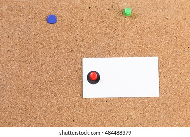 Blank white paper with red push pin. cork board