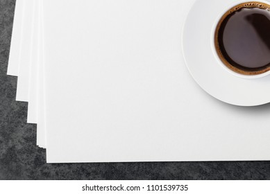 Blank white paper sheets and a cup of coffee.