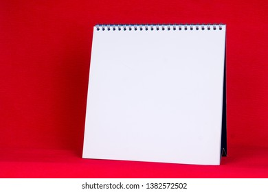 blank white paper spiral calendar with red background