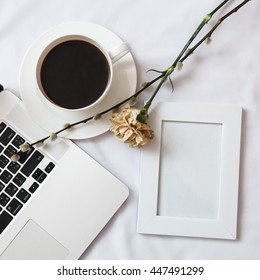 Blank white photo frame with coffee cup, laptop and flowers on white background, top view -  composition for instagram, social media, digital marketing, advertising, sales and holidays publications.