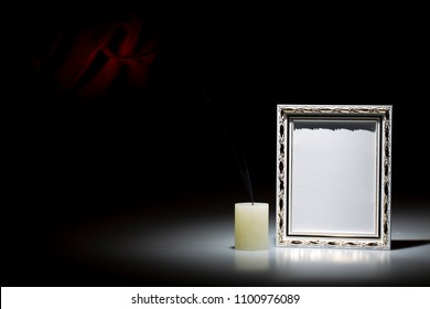 Blank white picture  frame with smoky candle on dark background with red decoration