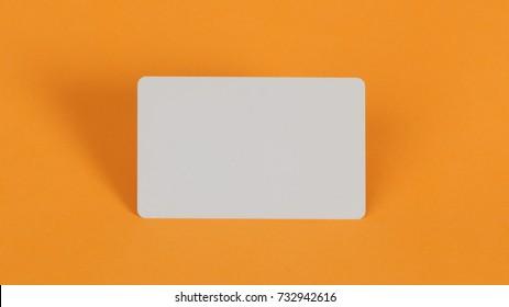 blank white plastic card on orange background