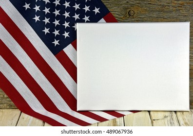 blank white rectangle canvas and American flag on wood
