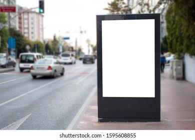 Blank white rectangular billboard at the roadside. Vehicles pass through the asphalt road.