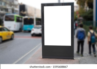 Blank white rectangular billboard at the roadside. On the left comes 2 teenagers on foot. Vehicles pass through the asphalt road.