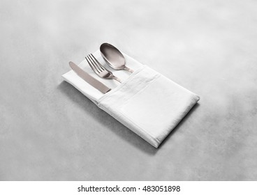 Blank white restaurant cloth napkin mock up with silver cutlery set, isolated. Knife fork and spoon in clear textile towel mockup template. Cafe branding identity clean napkin surface for logo design.