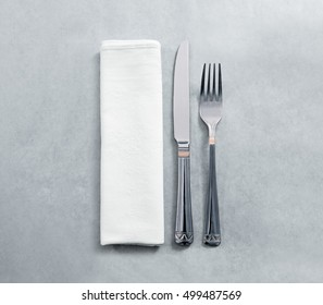 Blank white restaurant napkin mockup with knife and fork, isolated. Cutlery near clear textile towel mock up template. Cafe branding identity clean napkin surface for logo design.