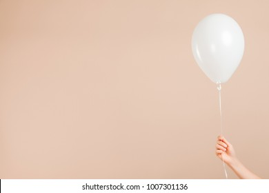 Blank white rubber inflatable balloon holds by human female hand on an abstract beige background. New Year event valentine and birthday celebration concept. Detailed close up studio shot