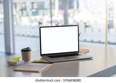 Blank white screen of a laptop and a notebook placed on the table at the office. Mock up.