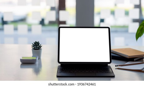 Blank white screen of a tablet and a notebook placed on the table at the office. Mock up.
