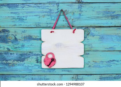 Blank white sign with heart padlock and key hanging on rustic teal blue wood door; Valentines Day holiday background with copy space