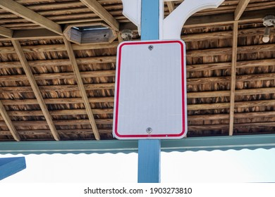 Blank white sign with red boarder attached to a blue post with the inside of the wooden ceiling as a background.