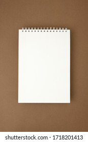 Blank white spiral notebook on brown surface. Mockup.