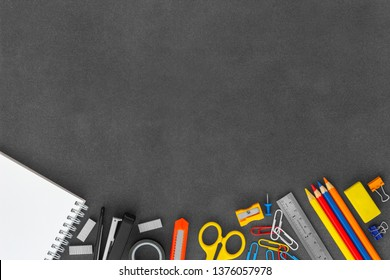 Blank white spiral paper notebook with scissors, stapler, cutter knife, paper clumps, paper clips, push pins, colored pencils, sharpener, eraser and ruler on empty dark background top view
