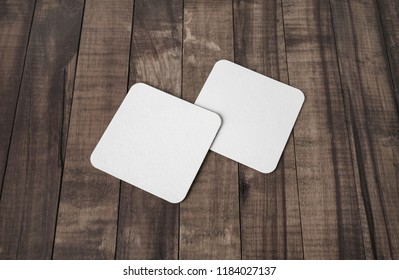 Blank white square beer coasters on wooden background.