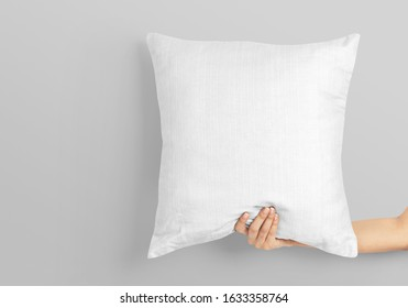 Blank white square pillow mockup holding by woman hand