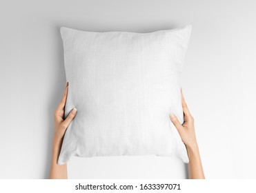 Blank white square pillow mockup holding with two hands by woman