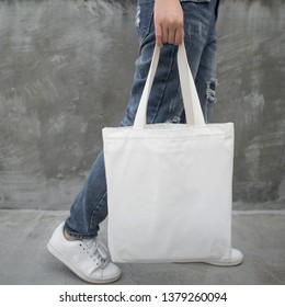 Blank white tote bag canvas fabric with handle mock up design. Close up of woman holding eco or reusable shopping bag on grunge grey wall. No plastic bag and ecology concept.