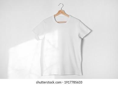 Blank white t-shirt against light grey background. Mock-up for branding.