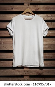 Blank white t-shirt hanging on the wooden background, with copy space